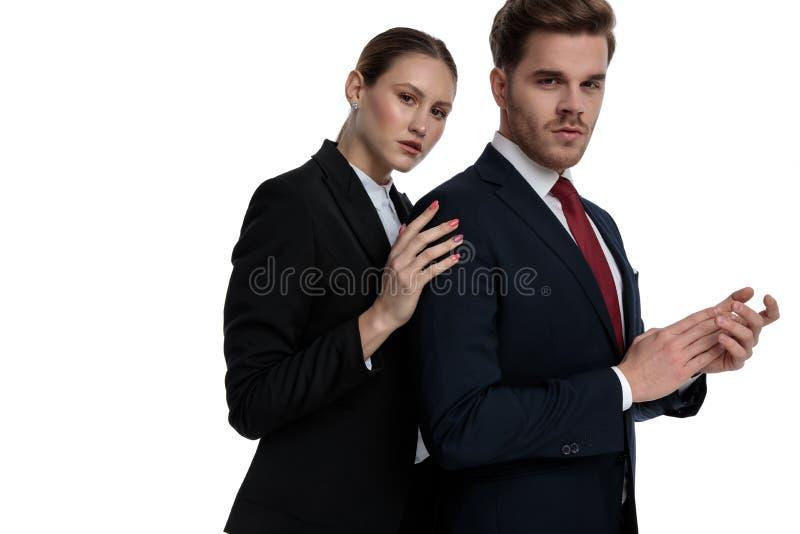 Couplez dans des costumes tenant des mains ensemble image stock
