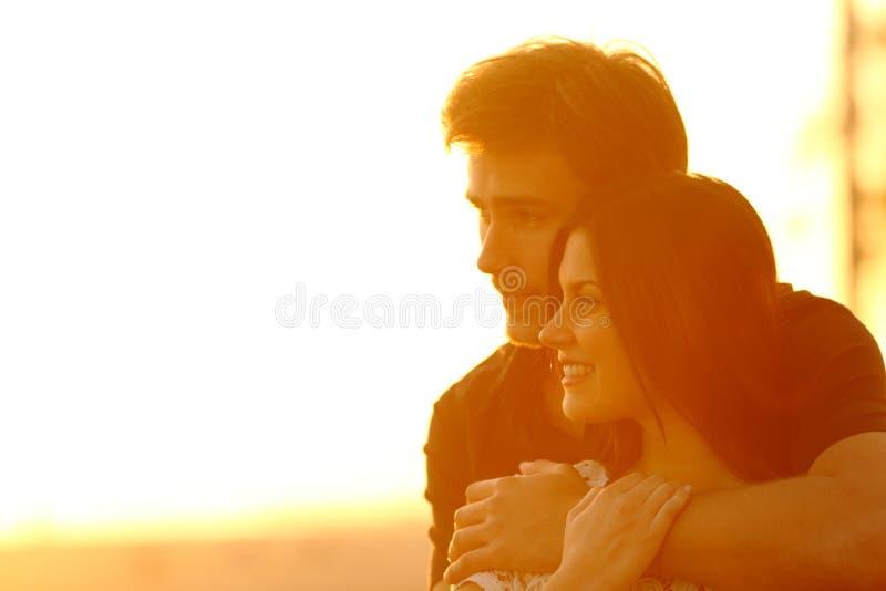 Couplez dans l'amour contemplant des vues au coucher du soleil photographie stock