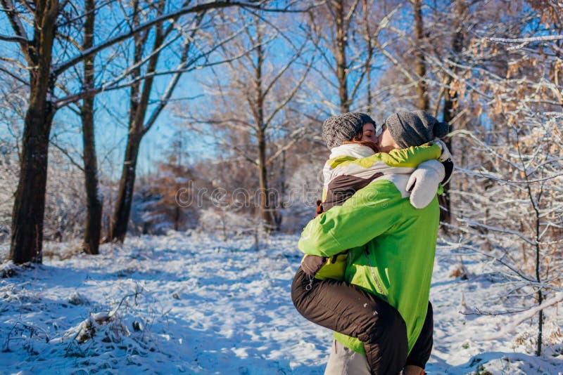 Couplez dans l'amour marchant et étreignant dans l'amie et des baisers de participation d'homme de forêt d'hiver Les jeunes ayant images stock