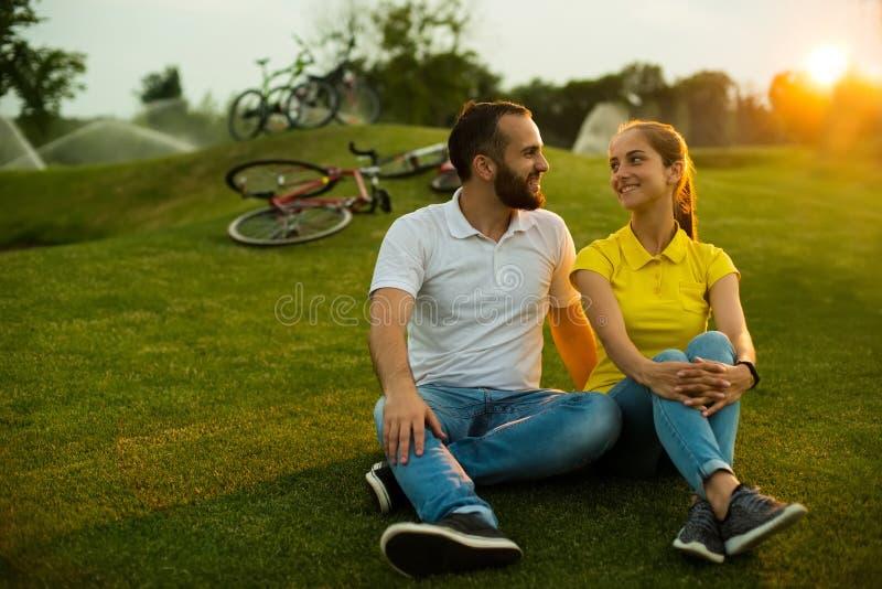 Couplez dans l'amour se reposant sur la pelouse verte photographie stock libre de droits