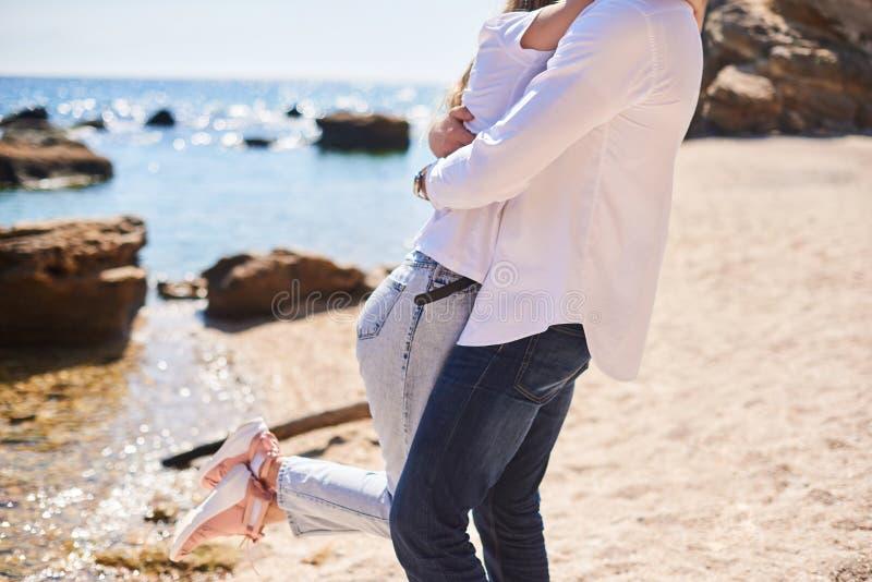 Couplez dans l'amour ?treignant sur une plage tropicale avec de l'eau turquoise et des roches ? l'arri?re-plan image libre de droits