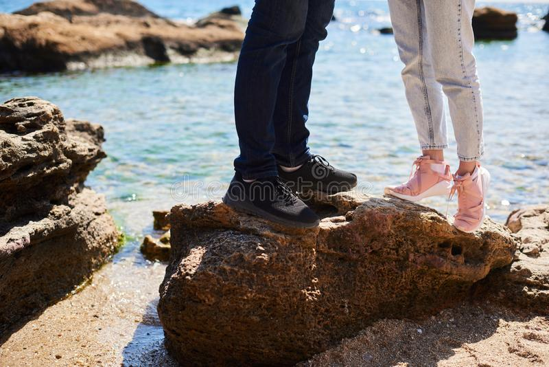 Couplez dans l'amour ?treignant sur une plage tropicale avec de l'eau turquoise et des roches ? l'arri?re-plan images stock