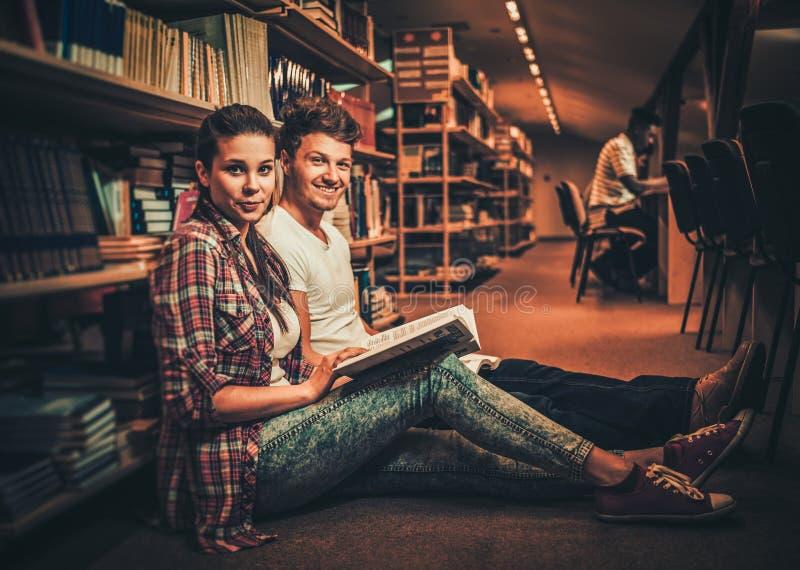 Couplez des étudiants étudiant à la bibliothèque universitaire photos libres de droits