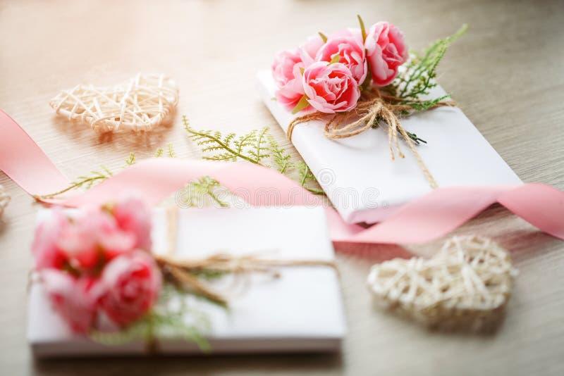 Couplez des boîte-cadeau enveloppés avec le papier blanc simple de métier et décorés du bouquet des roses et du groupe vert photos stock