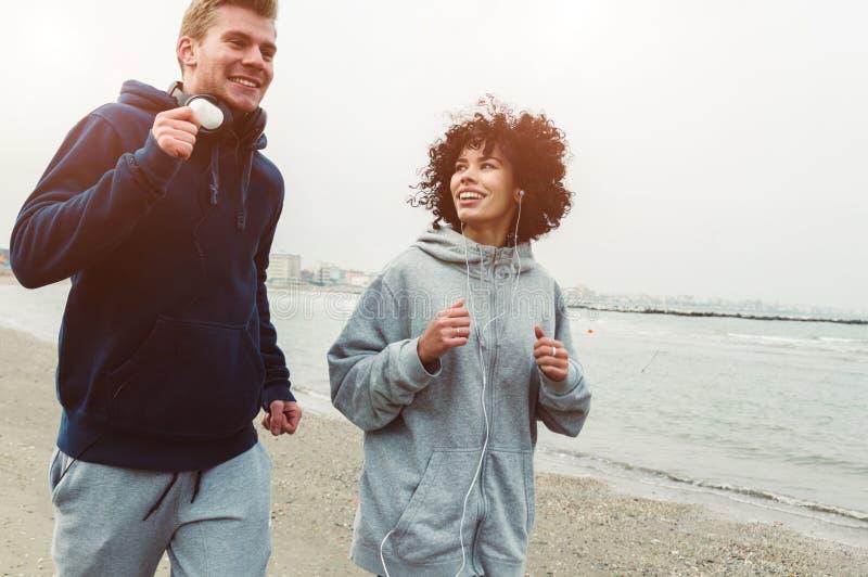 Couplez des coureurs s'exerçant à la plage en hiver photo stock