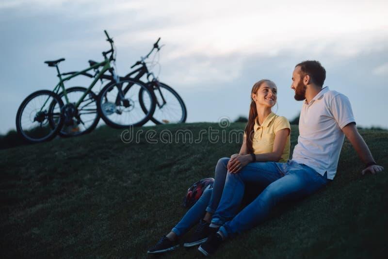 Couplez des cyclistes dans l'amour se reposant sur la colline verte image stock