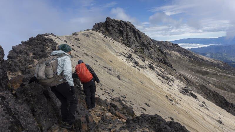 Couplez des grimpeurs marchant vers le sommet du volcan de Guagua Pichincha près de la ville de Quito photo stock