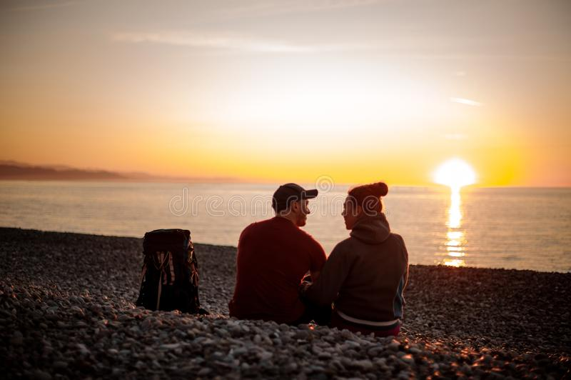 Couplez des randonneurs avec les sacs à dos se reposant sur la plage et regardant la mer photo libre de droits