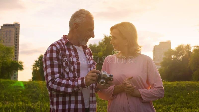 Couplez des retraités observant des photos sur la caméra, en souriant entre eux, date photographie stock
