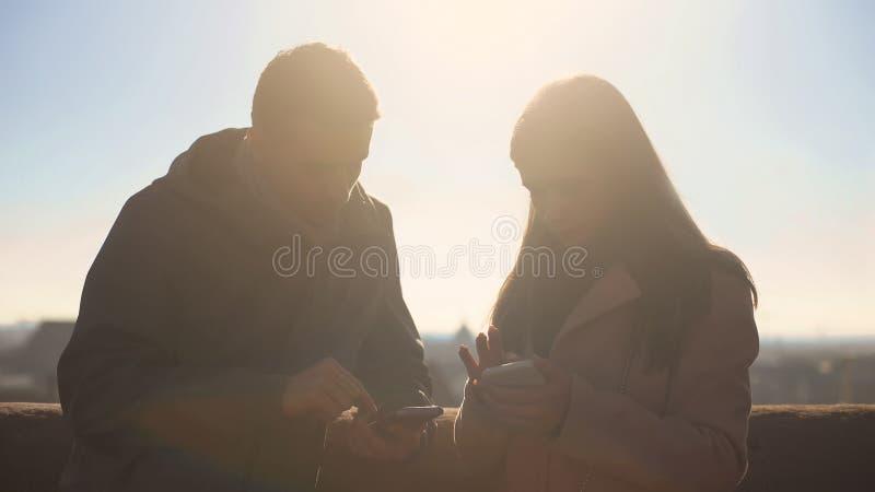 Couplez des touristes observant des photos de promenade sur des smartphones, en se tenant sur le dessus de toit photographie stock libre de droits