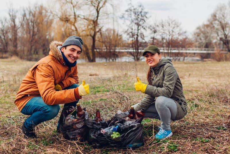 Couplez des volontaires a nettoyé les déchets en parc Les gens ont pris des déchets et résultat de représentation avec le pouce   photographie stock libre de droits
