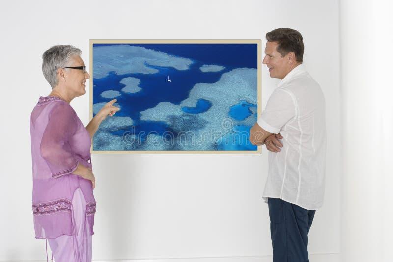 Couplez discuter des plans de vacances contre le mur blanc avec la photographie image stock