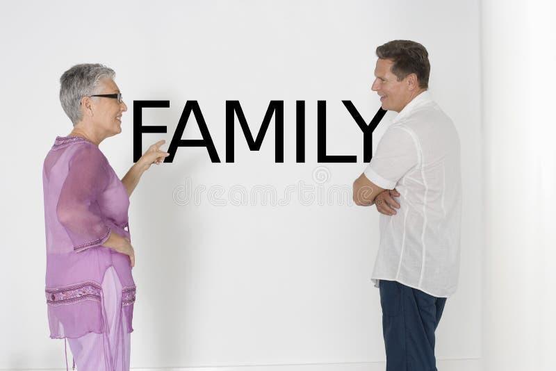 Couplez discuter des questions de famille contre le mur blanc avec le texte anglais photos stock