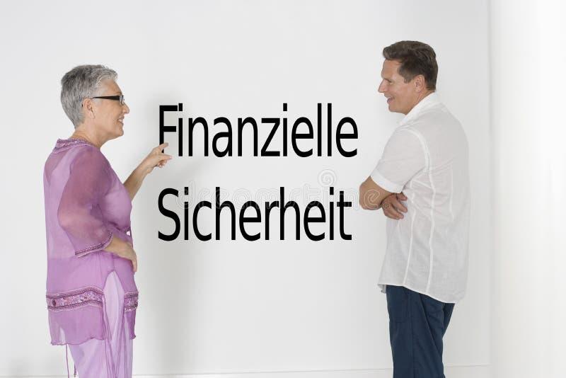 Couplez discuter la sécurité contre le mur blanc avec le texte allemand Finanzielle Sicherheit images libres de droits