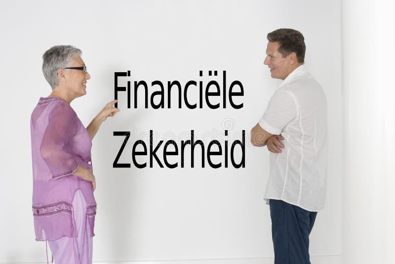 Couplez discuter la sécurité contre le mur blanc avec le zekerheid néerlandais de financiële des textes photo stock