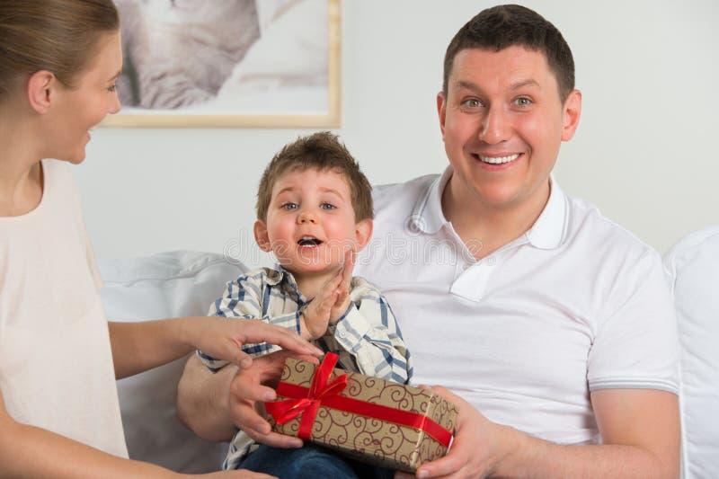 Couplez donner le cadeau à leur petit fils dans le salon images libres de droits