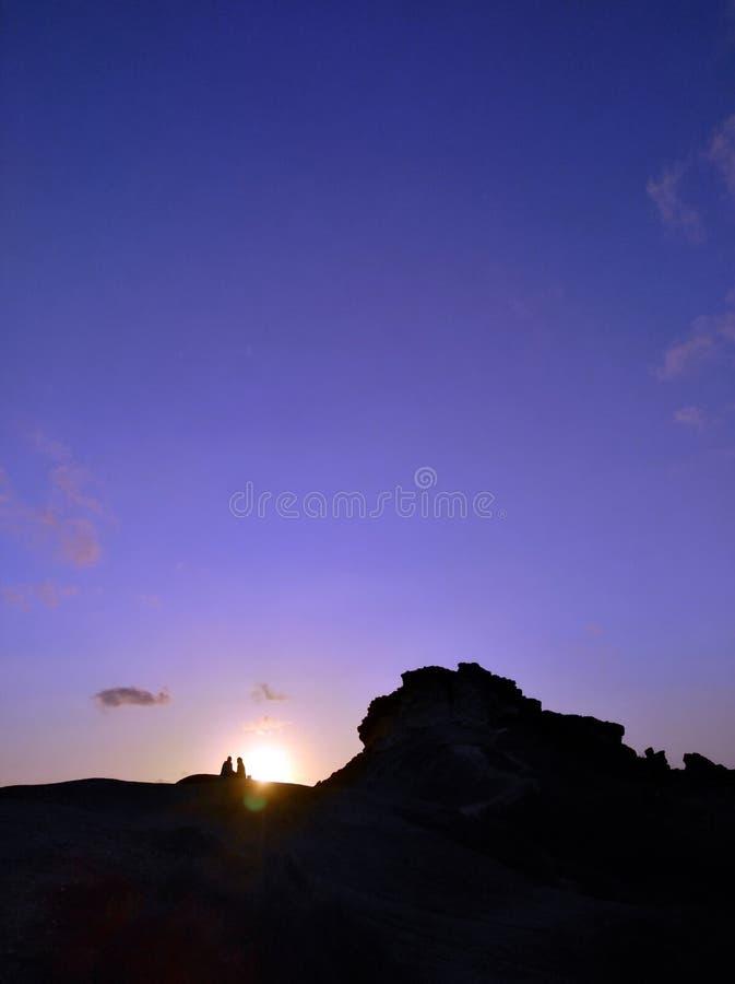 Couplez en haut de la montagne et du coucher du soleil photo stock