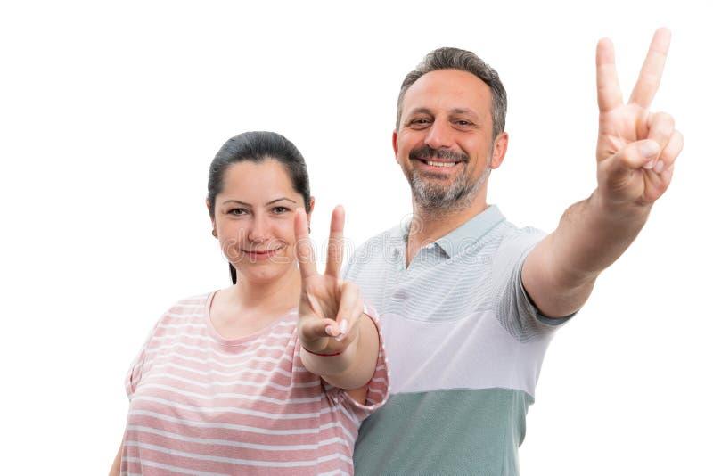 Couplez faire le signe de paix ou de victoire photos stock