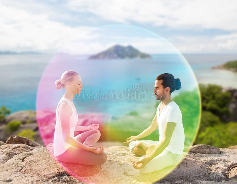 Couplez faire le yoga dans la pose de lotus avec l'aura d'arc-en-ciel photo libre de droits