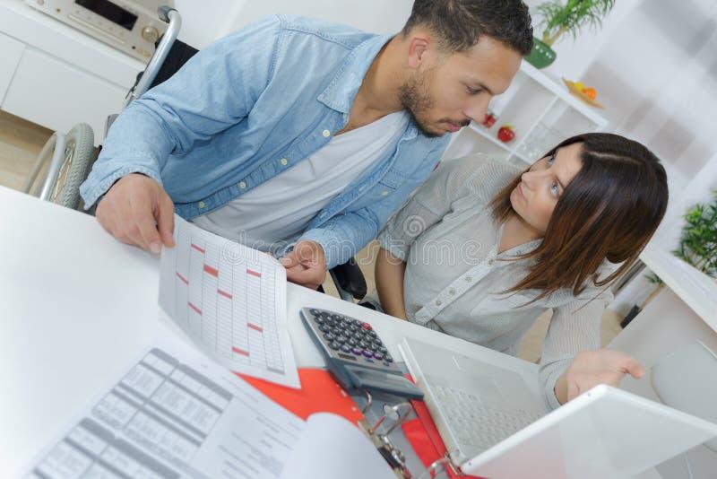 Couplez faire leurs comptes avec les feuilles de calcul et l'ordinateur portable image libre de droits