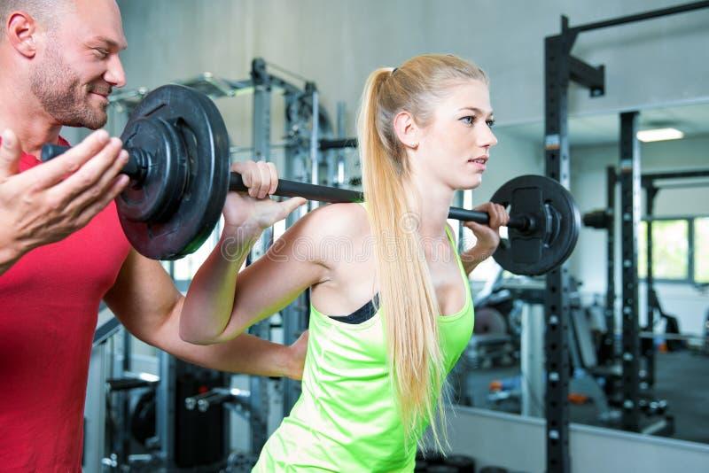 Couplez faire une séance d'entraînement de forme physique dans le gymnase de sport photographie stock libre de droits