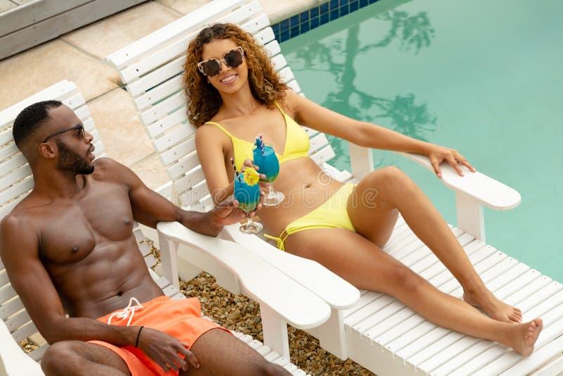 Couplez griller des verres de cocktail tout en détendant sur un canapé du soleil près de la piscine photos libres de droits