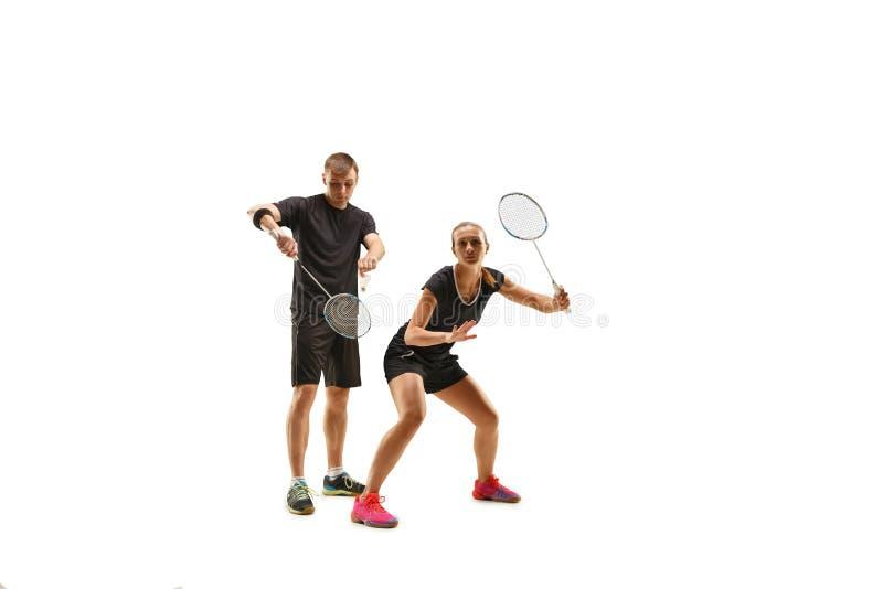 Couplez jouer avec des raquettes de badminton d'isolement sur le blanc photographie stock