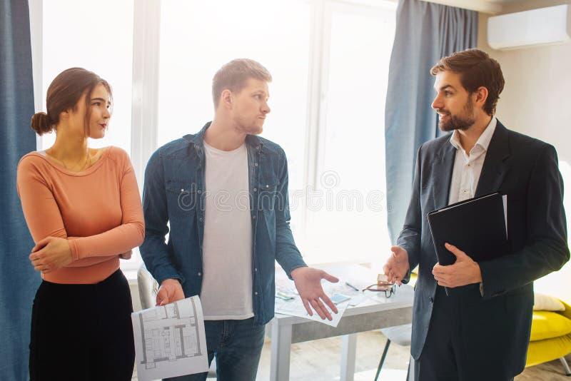 Couplez l'appartement d'achat ou de loyer ensemble Ils regardent confus l'agent immobilier Cliets ont des doutes Regard sérieux d photo libre de droits