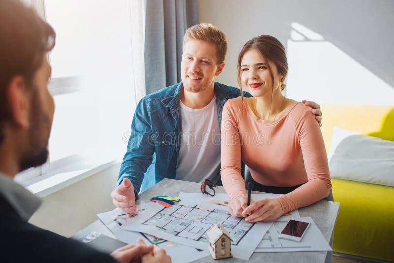 Couplez l'appartement d'achat ou de loyer ensemble Ils se reposent devant l'agent immobilier et le regardent Femme d'étreinte de  images stock