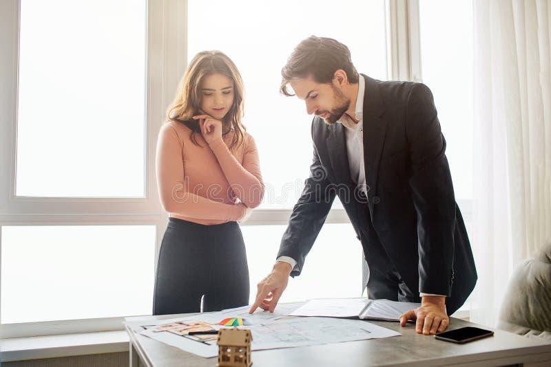 Couplez l'appartement d'achat ou de loyer ensemble Ils se tiennent sur la table et tiennent là le plan Regard de jeune homme à lu photographie stock