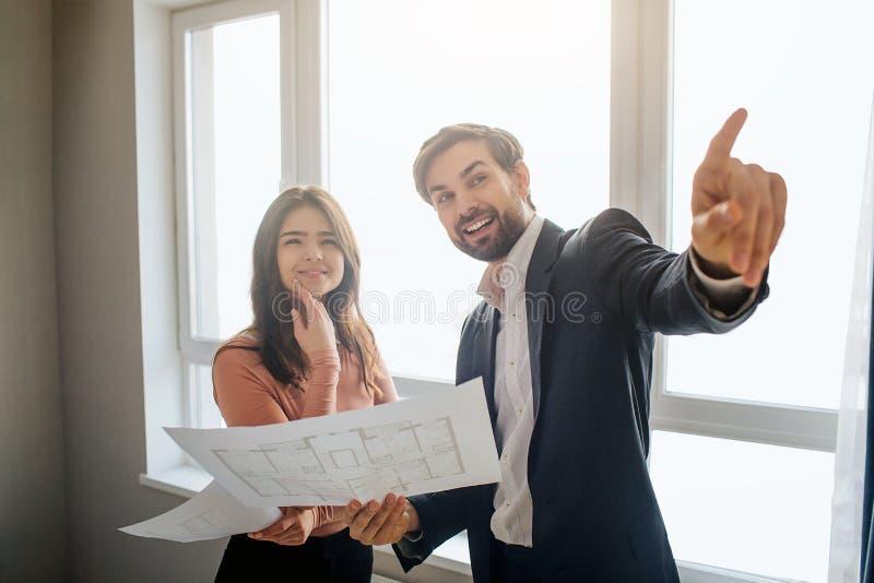 Couplez l'appartement d'achat ou de loyer ensemble Plan de prise de jeune homme à disposition et point en avant Support ensemble  photo stock