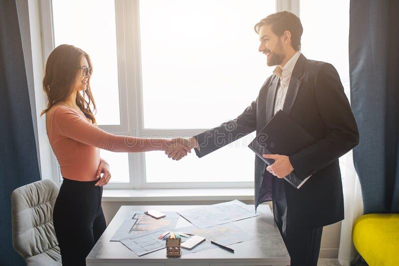 Couplez l'appartement d'achat ou de loyer ensemble Se serrer la main Jeune homme et femme de betwee d'affaire d'affaires Gens gai photos stock