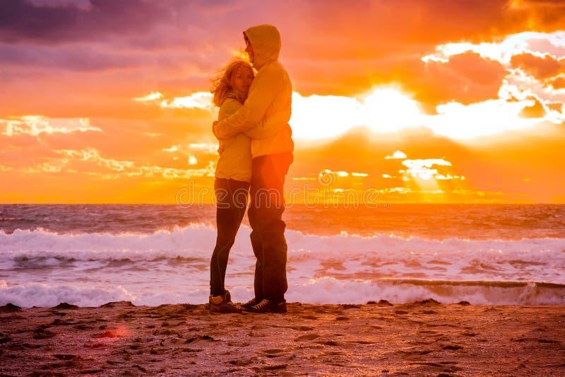 Couplez l'homme et la femme étreignant dans l'amour restant sur le bord de la mer de plage photographie stock libre de droits