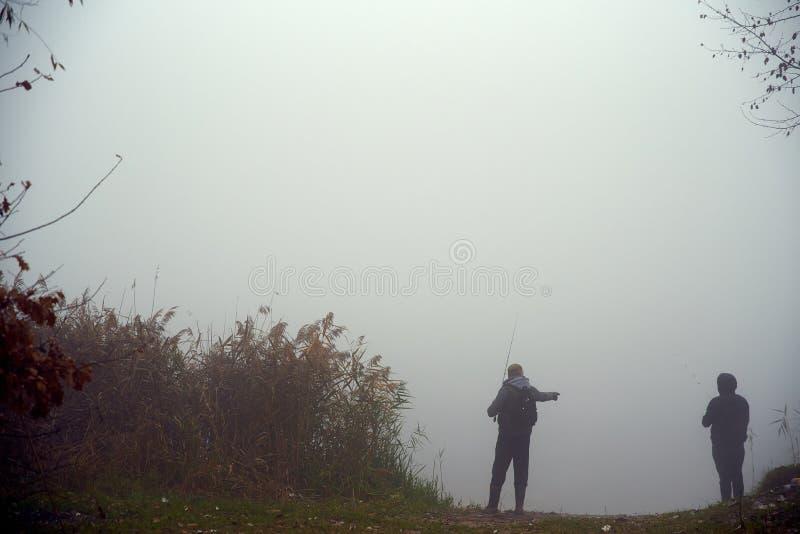 Couplez l'homme et les pêcheurs de femme pêchent des poissons sur une canne à pêche dans le lac image libre de droits
