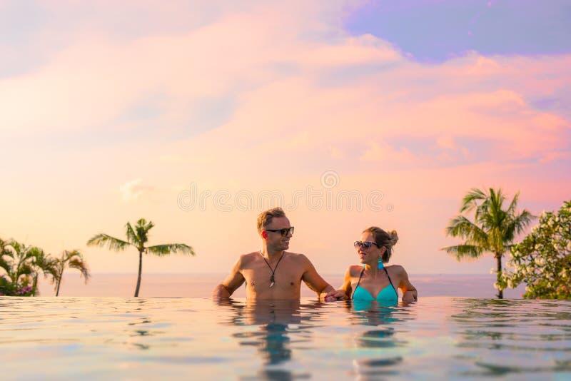 Couplez la détente dans la piscine d'infini du lieu de villégiature luxueux exotique photographie stock libre de droits