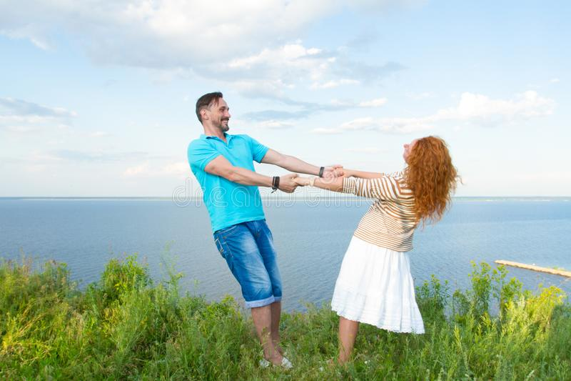 Couplez la danse dans l'herbe au-dessus du fond de lac et de ciel Tiré de la jeune femme rouge attirante de cheveux tenant des ma image stock