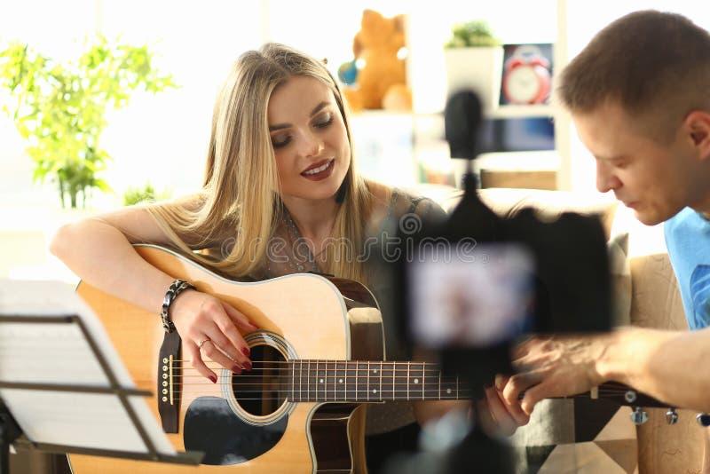 Couplez la leçon à la maison de enregistrement de blog de vidéo musicale photos stock