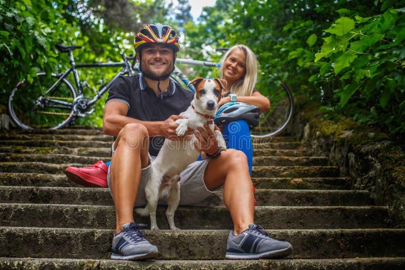 Couplez la pose avec le chien de ther après l'équitation de bycicle image libre de droits