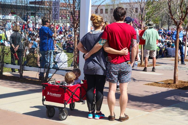 Couplez la position de nouveau à l'appareil-photo avec des bras autour d'un un autre et deux enfants dans le chariot chez mars po photographie stock libre de droits