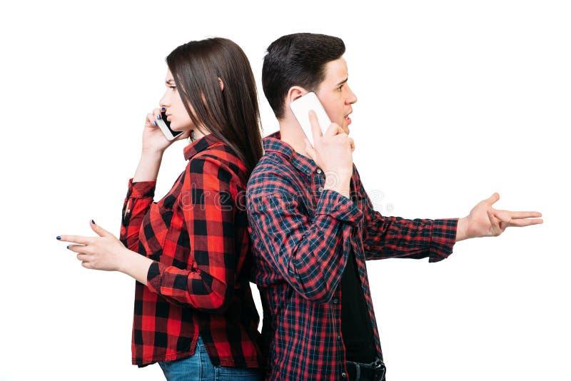 Couplez la position de nouveau au dos, parlant par des téléphones images stock