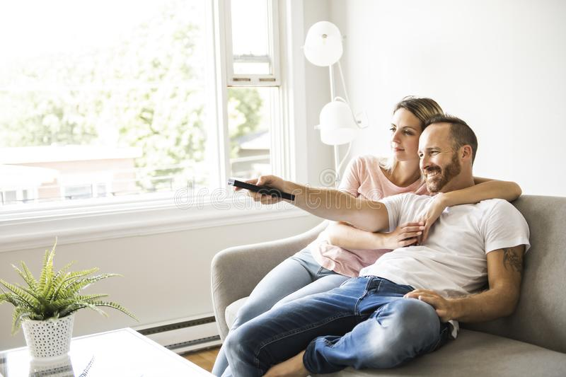 Couplez la TV de observation à la maison se reposant dans un divan confortable dans le salon à la maison photos libres de droits