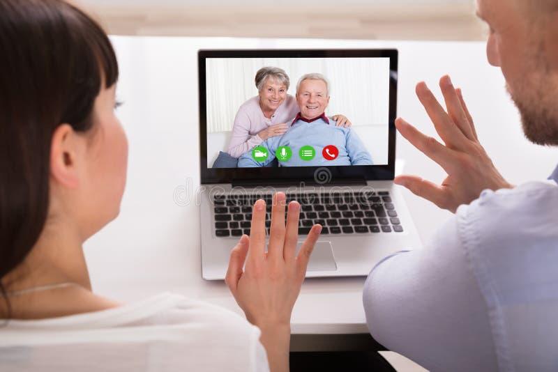 Couplez la vidéoconférence sur l'ordinateur portable images stock