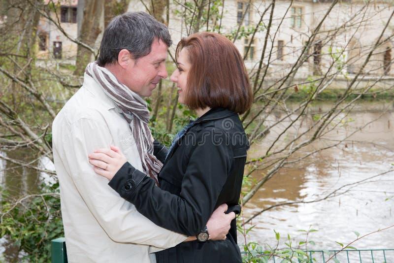 couplez le baiser se faisant face dans l'oeil près de la rivière de lac de ville photos libres de droits