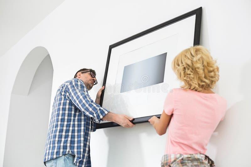 Couplez le cadre de tableau accrochant sur le mur dans la nouvelle maison photographie stock libre de droits