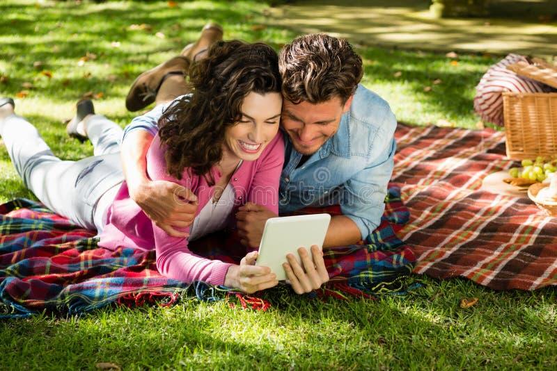 Couplez le mensonge sur la couverture de pique-nique et à l'aide du comprimé numérique image stock