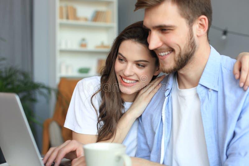 Couplez le pointage tout en travaillant ensemble sur l'ordinateur portable image stock
