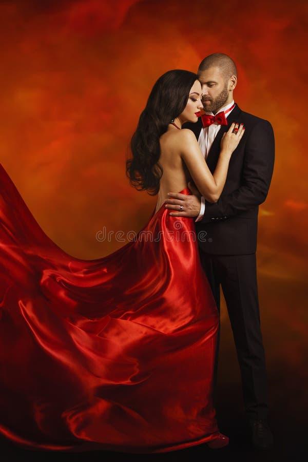 Couplez le portrait de mode, l'homme élégant et la femme dans la robe rouge images libres de droits