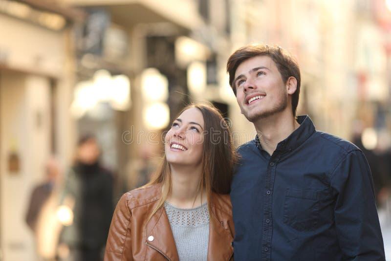 Couplez le regard en haut dans la rue d'une ville images stock