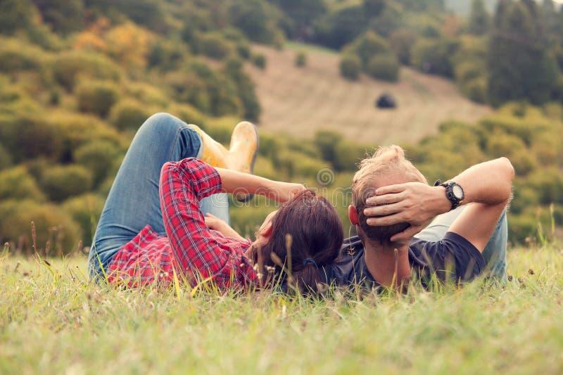 Couplez le repos dans l'herbe verte sur la colline dans le côté de pays photos stock