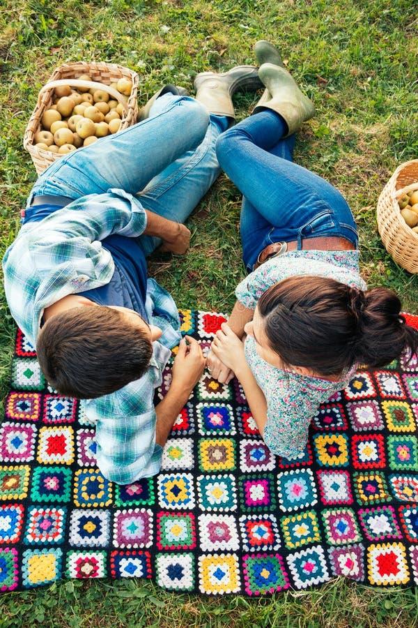Couplez le repos sur une couverture sur l'herbe en automne photographie stock libre de droits